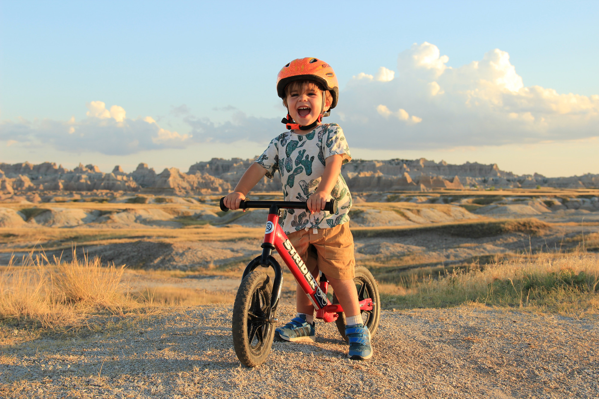 Young boy smiling on red 12 classic in front of beautiful landscape