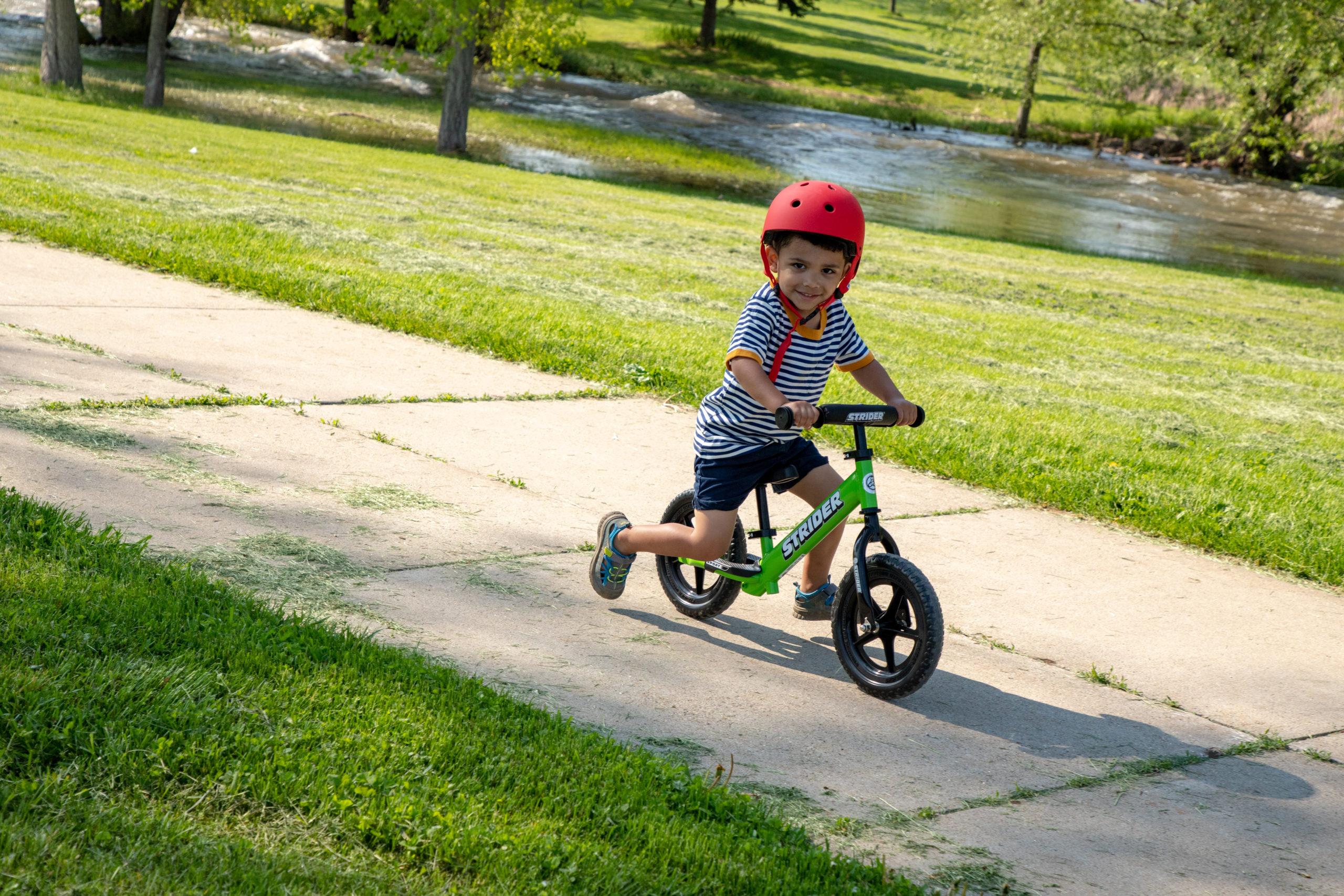Young boy striding on sidewalk on green 12 sport