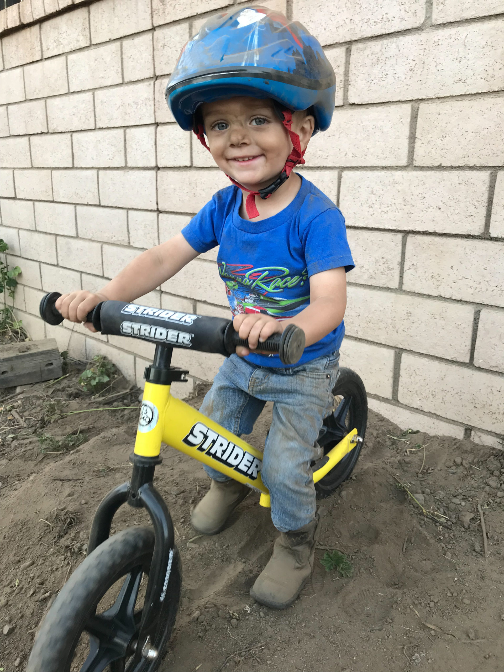 Young boy covered in dirt riding yellow 12 Sport