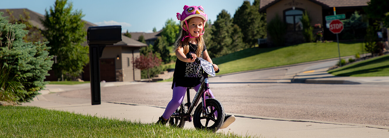 A child in a silly pink helmet rides a purple Strider 12 Pro balance bike down the sidewalk in a residential setting