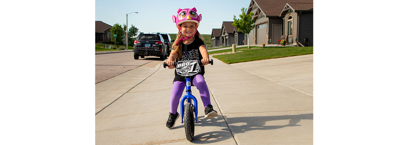 Smiling girl riding ultra blue 12 Pro down the sidewalk