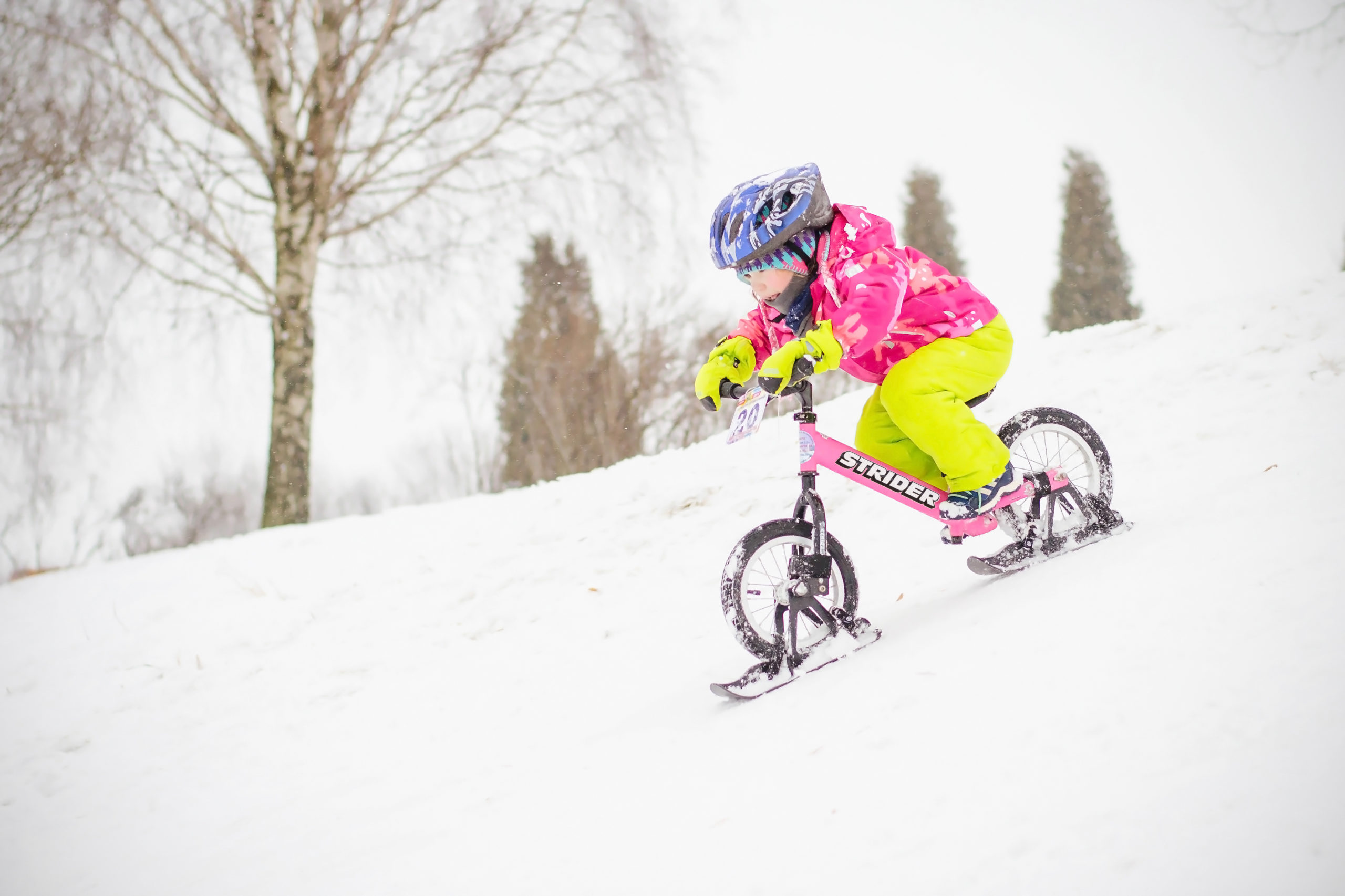 Girl riding down snow hill on pink 12 Sport with Strider skis attached