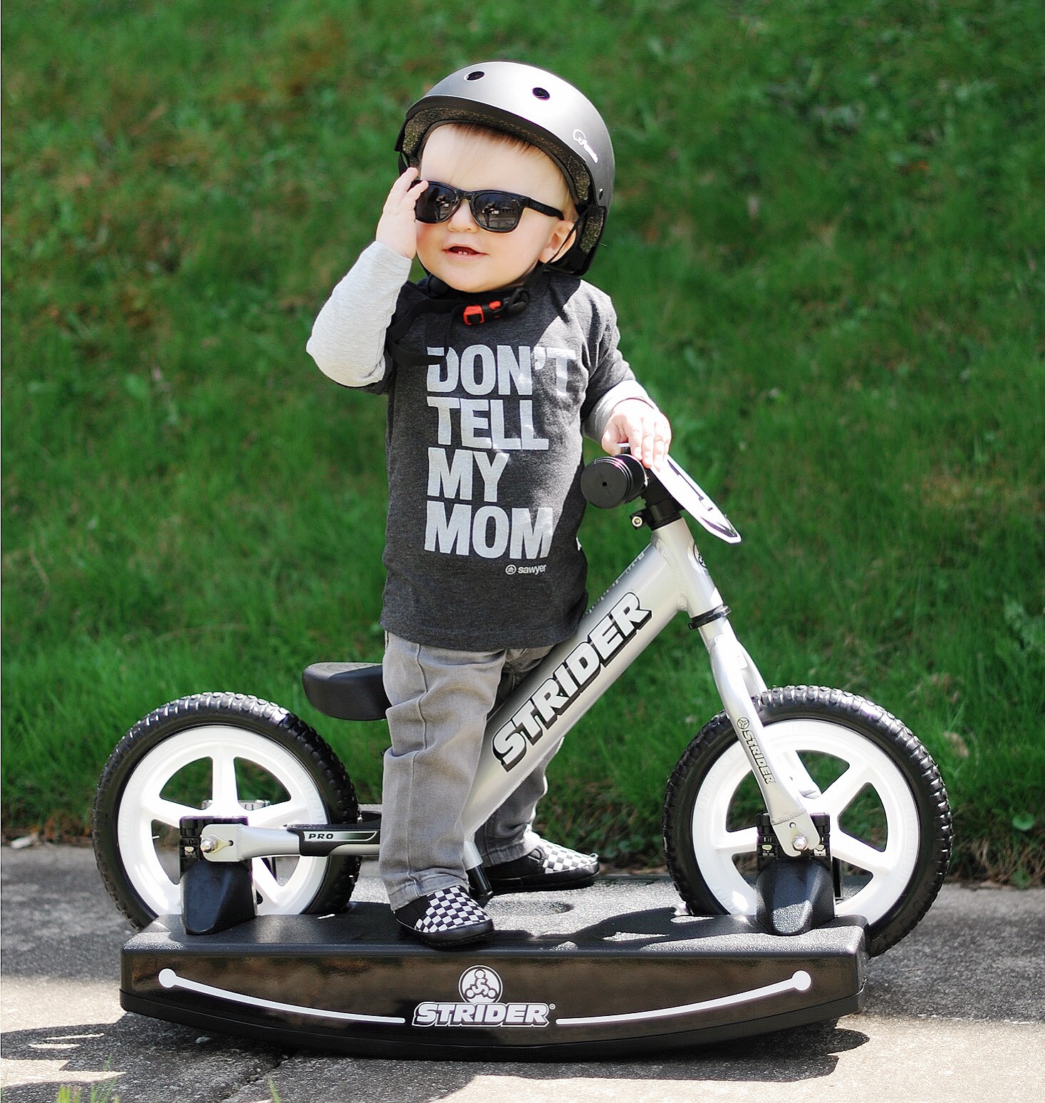 Young baby with sunglasses standing over silver 12 Pro 2-in-1 Rocking Bike