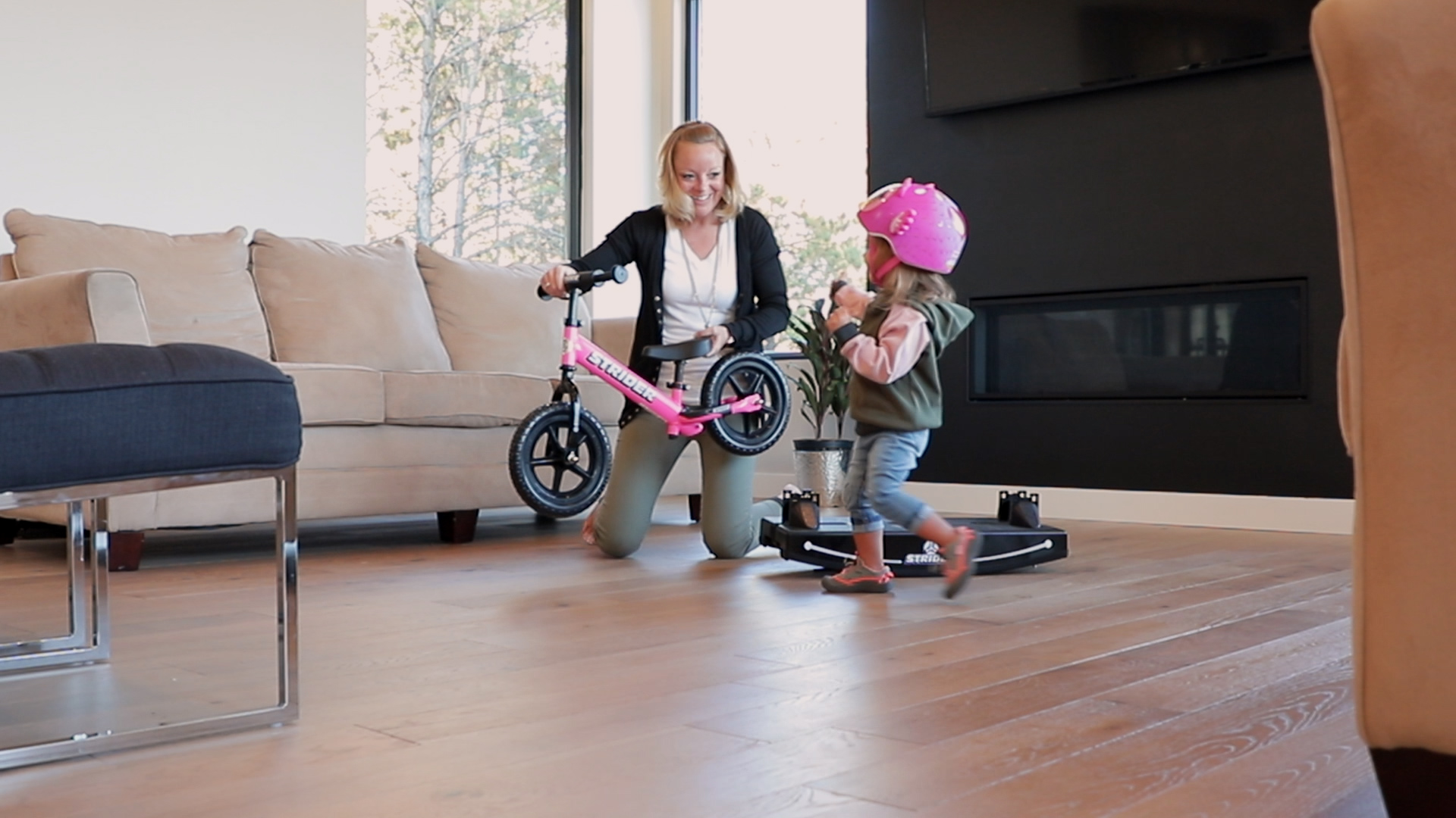 Mom removing pink 12 Sport 2-in-1 Rocking bike from base for little girl to ride