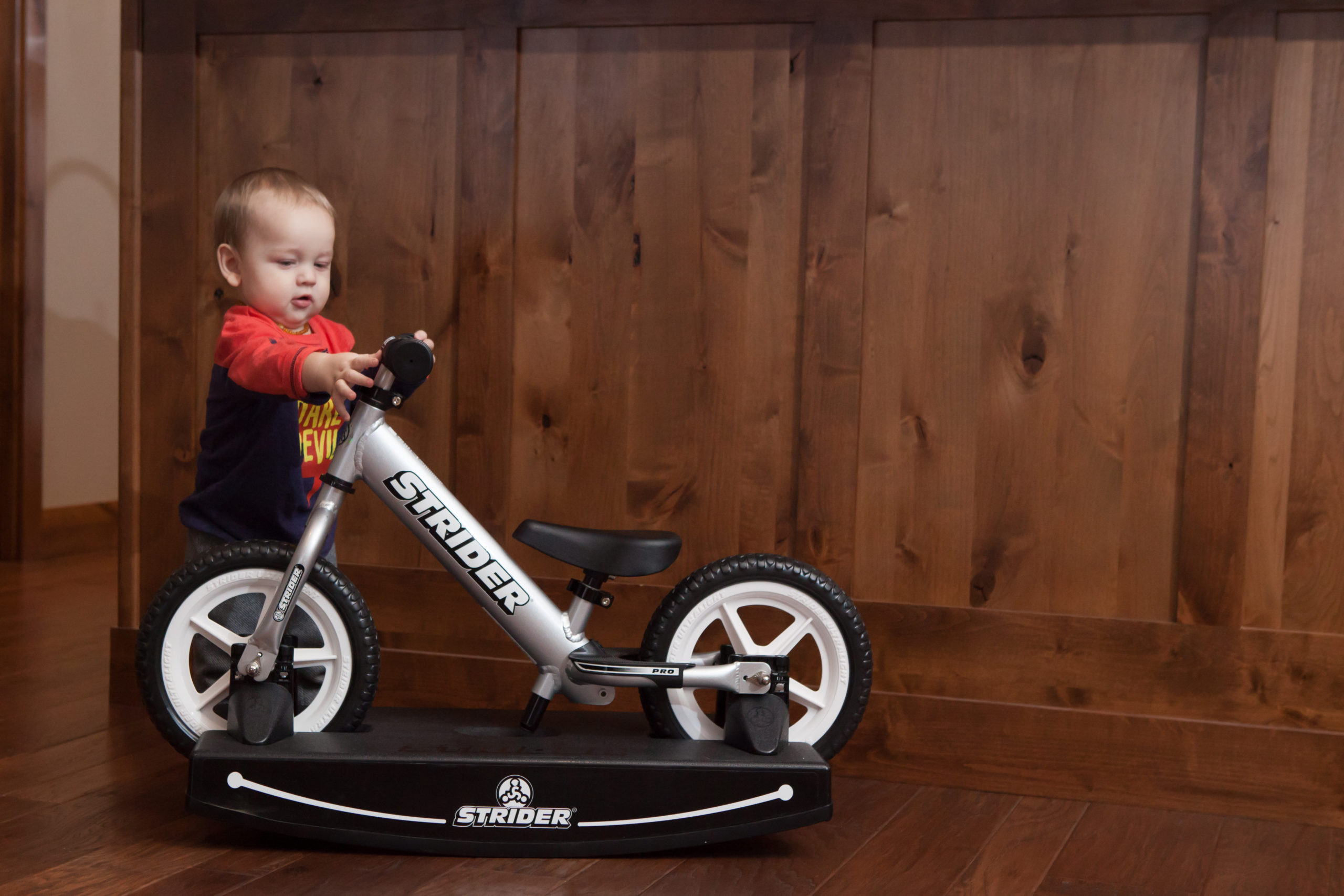 Little baby holding onto handlbars looking at 12 Pro 2-in-1 Rocking Bike
