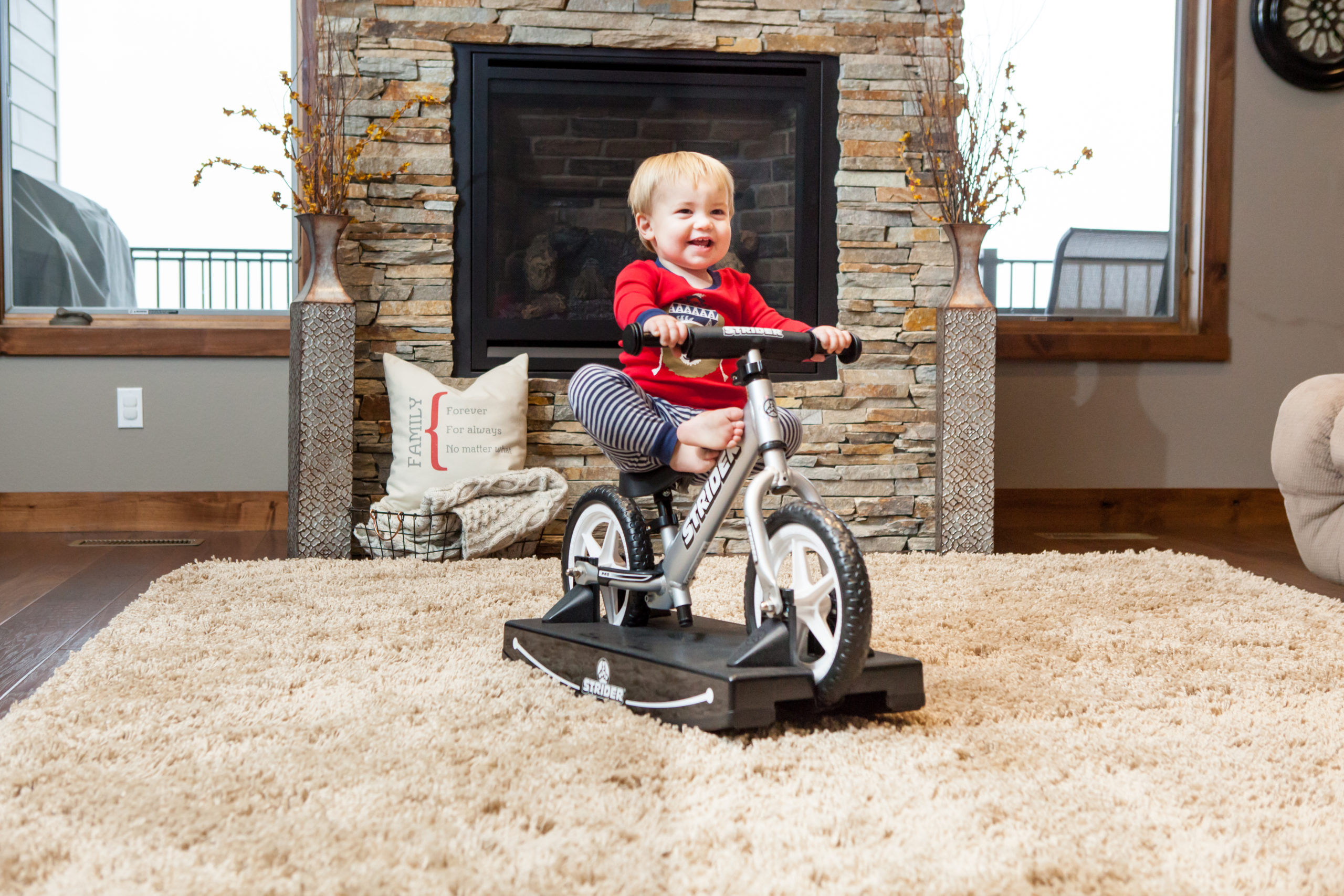 Little baby smiling with feet up on 12 Pro 2-in-1 Rocking Bike