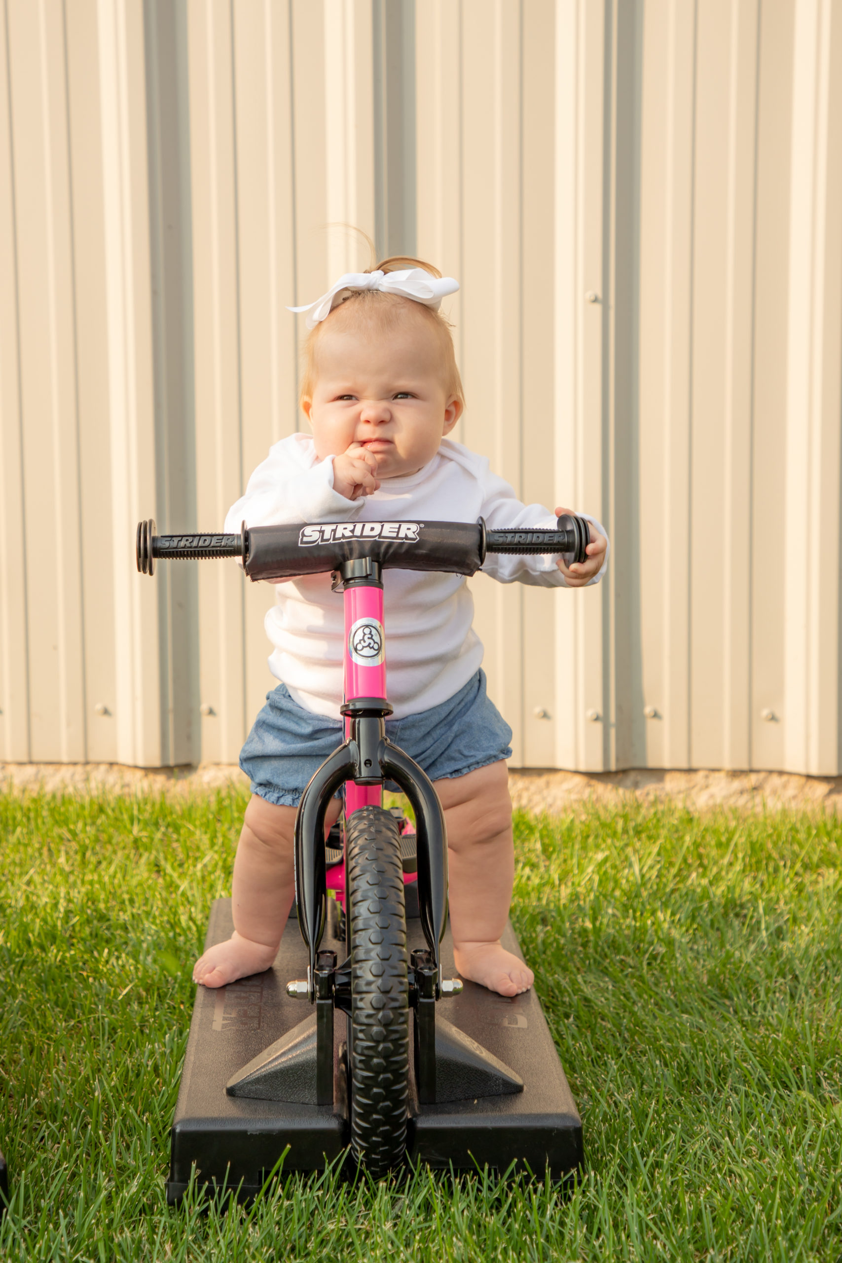 Little baby girl with scrunched face on pink 12 Sport 2-in-1 Rocking Bike