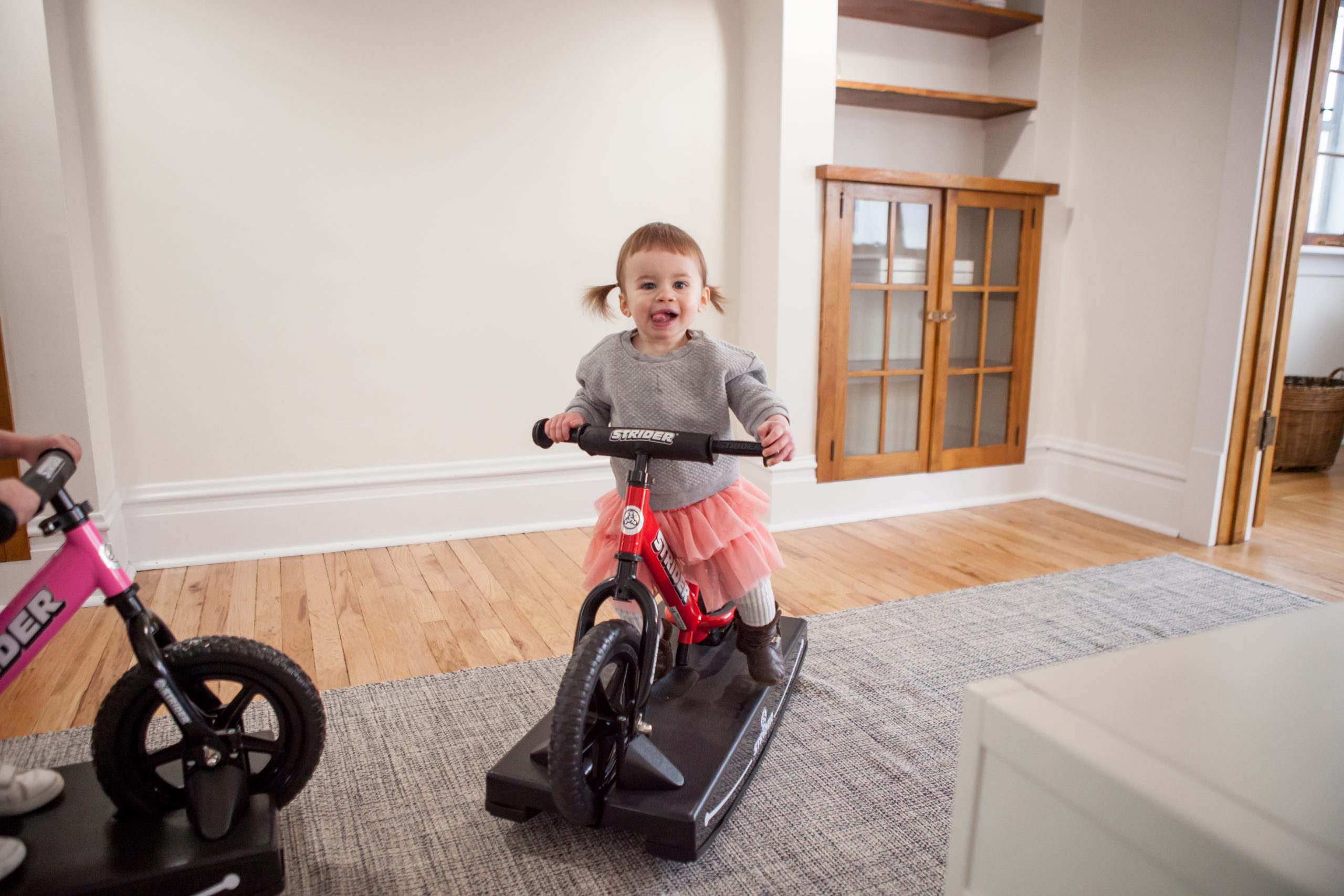 Little girl with tongue out rocking on red 12 Sport 2-in-1 Rocking Bike