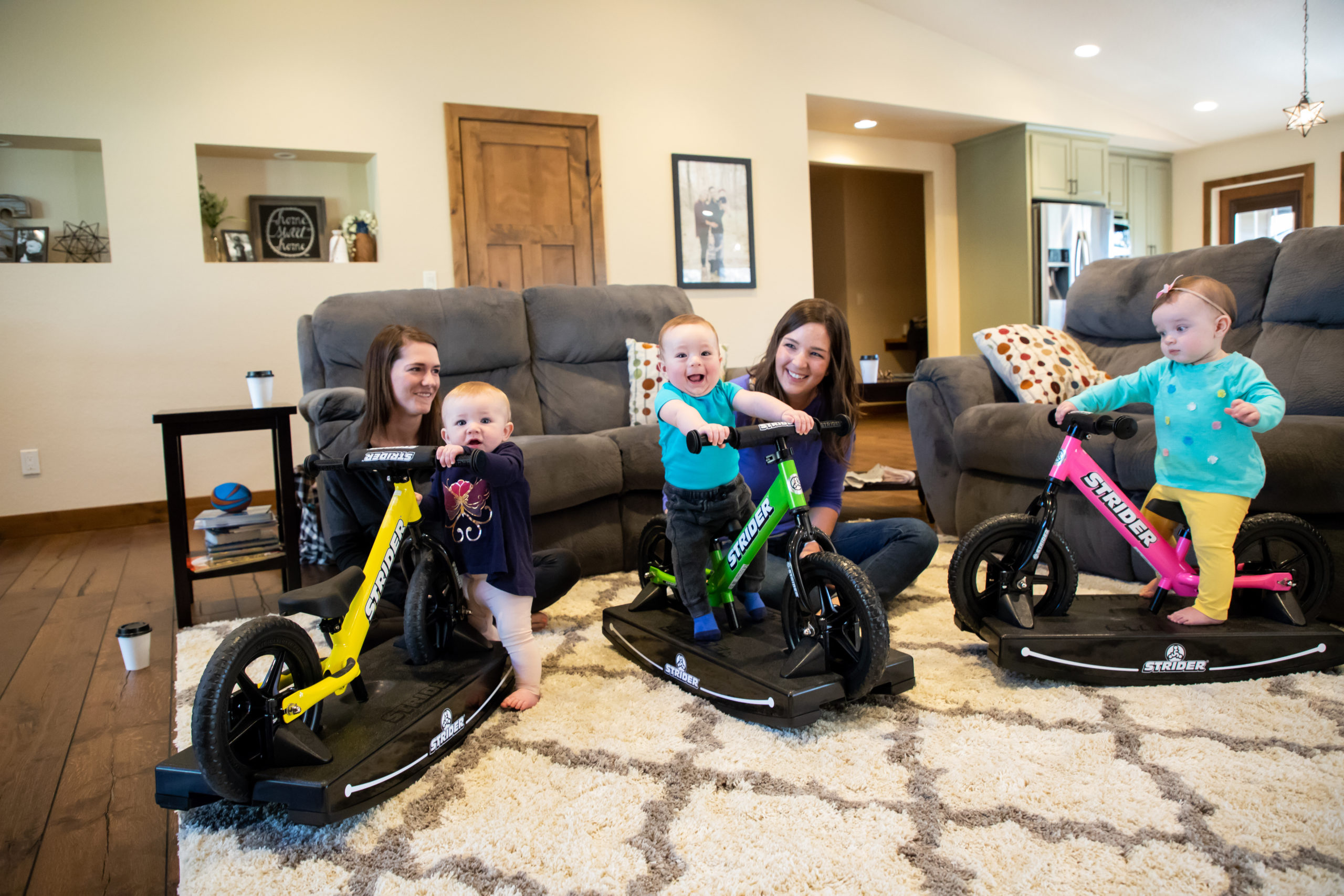 Three young babies playing on 2-in-1 Rocking Bikes with their moms watching and smiling