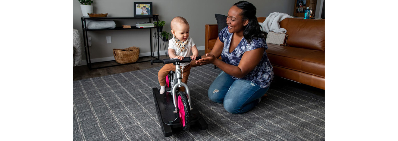 A baby on a silver Pro Rocking Bike plays with Mom