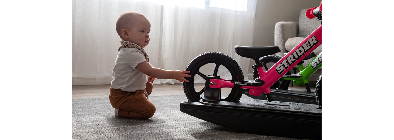 A baby checking out a pink Rocking Bike
