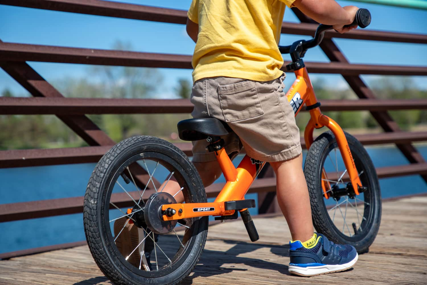 Close-up view of a Totally Tangerine Strider 14x balance bike with a body of water in the background