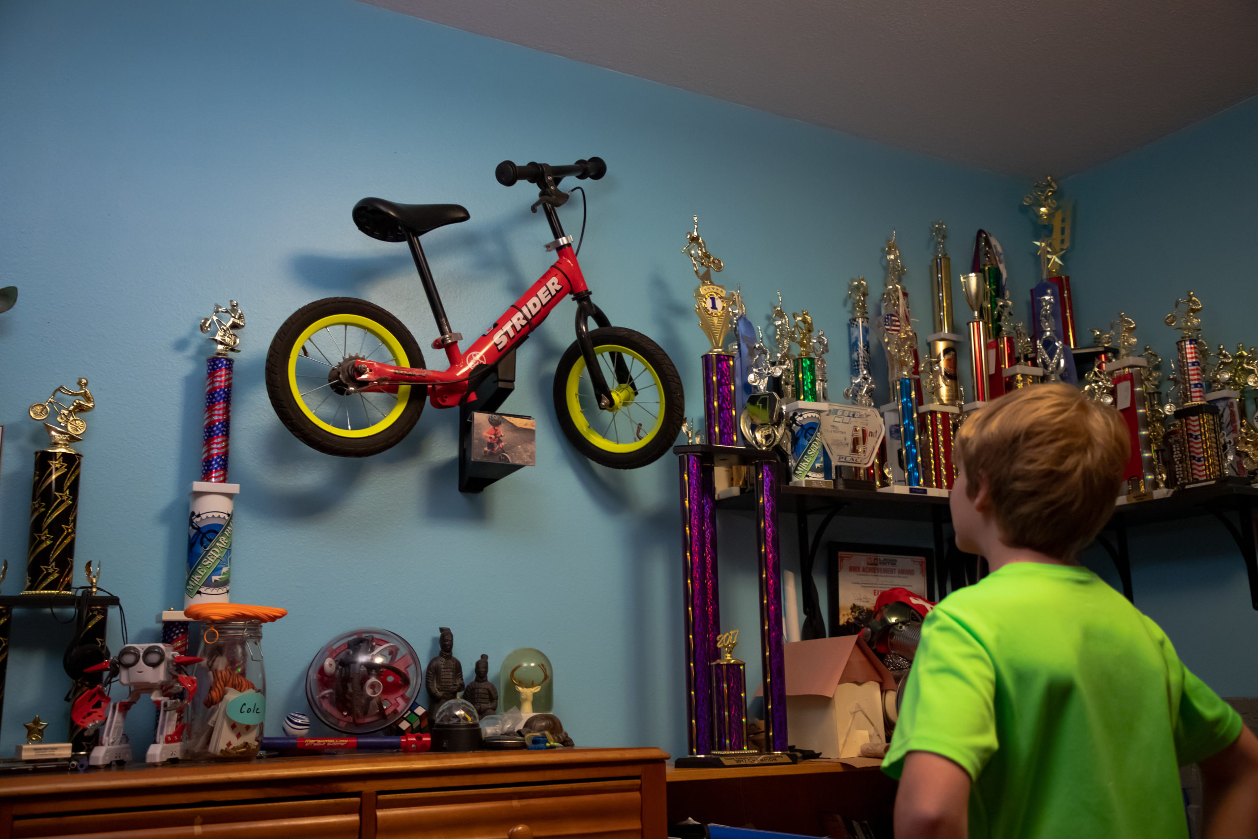 Memory mount hung up on wall in boy's bedroom with old red 12 Classic bike and boy looking at it proudly