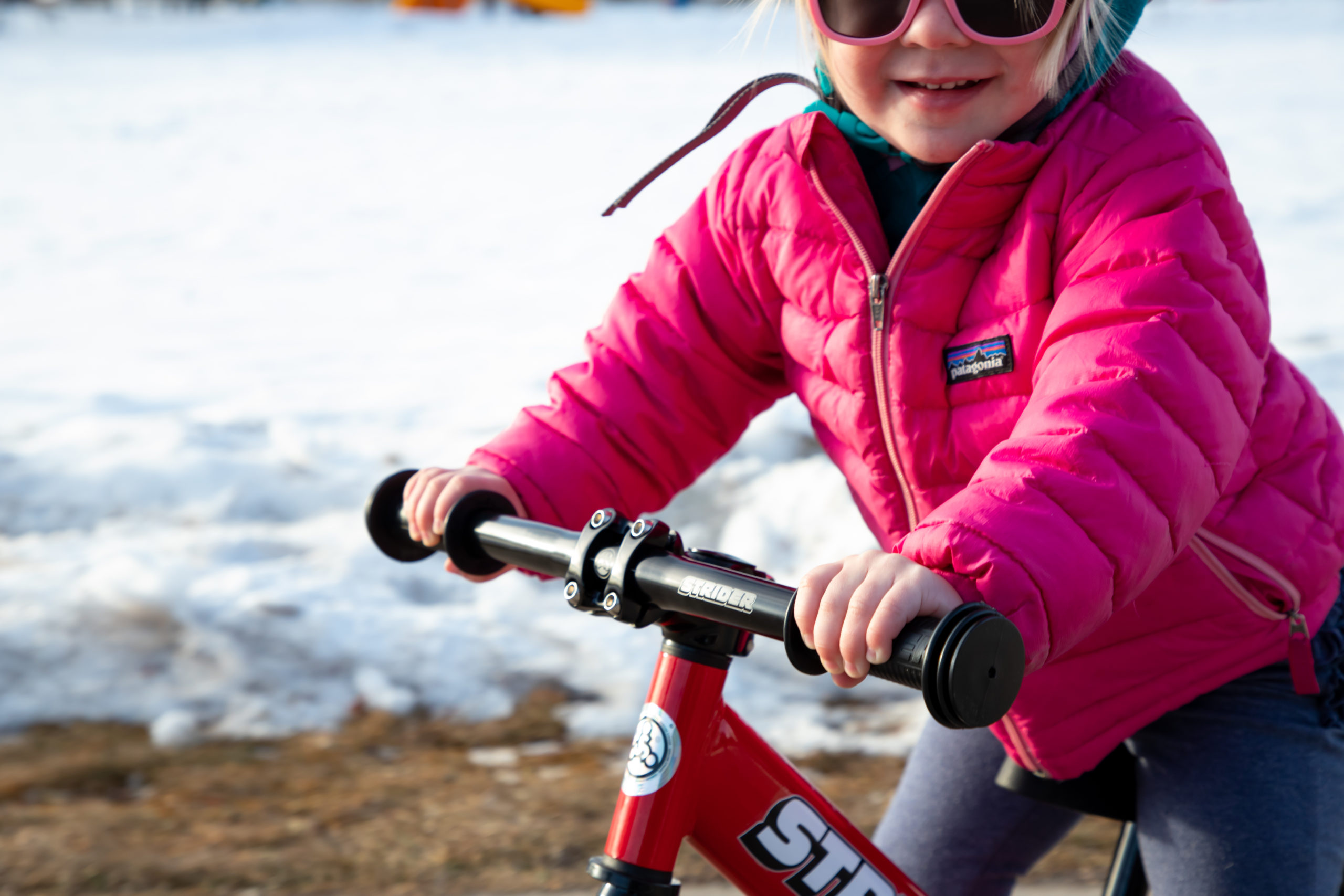 Close-up of Girl riding red 12 Sport with Strider Aluminum Flat Handlebar