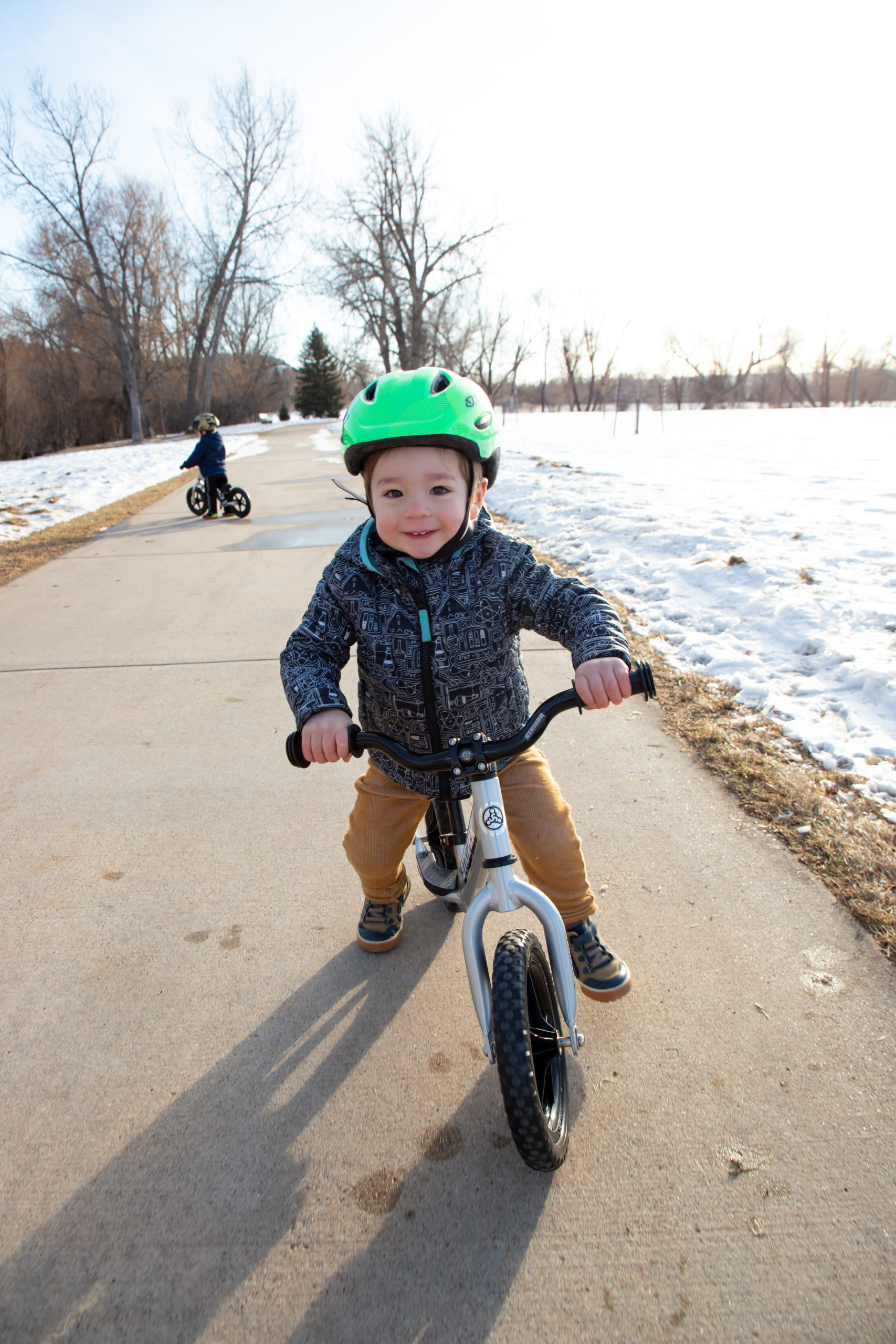 Young toddler boy striding with a smile on silver 12 Pro with Strider Aluminum Riser Bars
