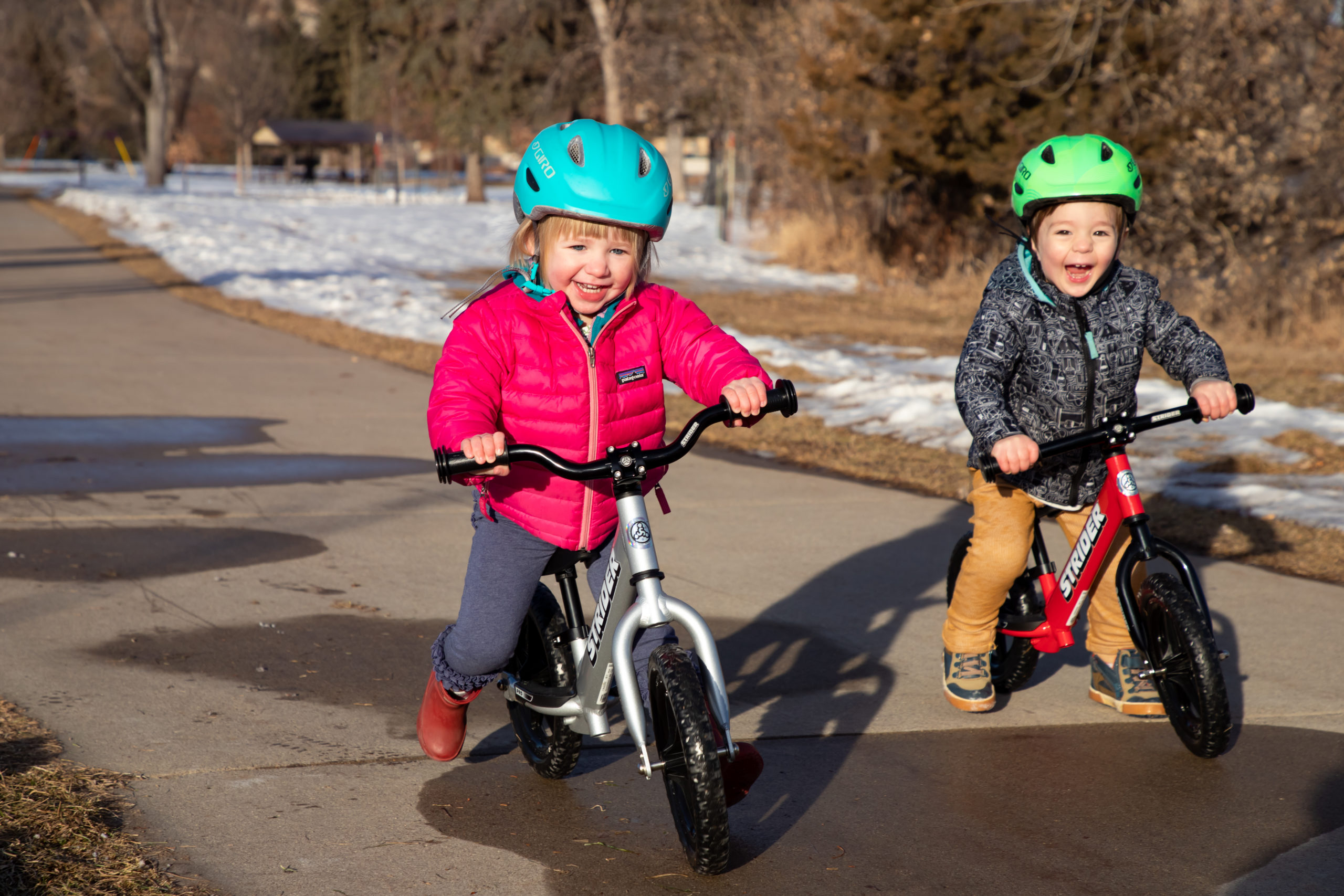 Young toddler boy striding with a smile on silver 12 Pro with Strider Aluminum Riser Bars next to young toddler boy smiling and striding on red 12 Sport with aluminum flat bars