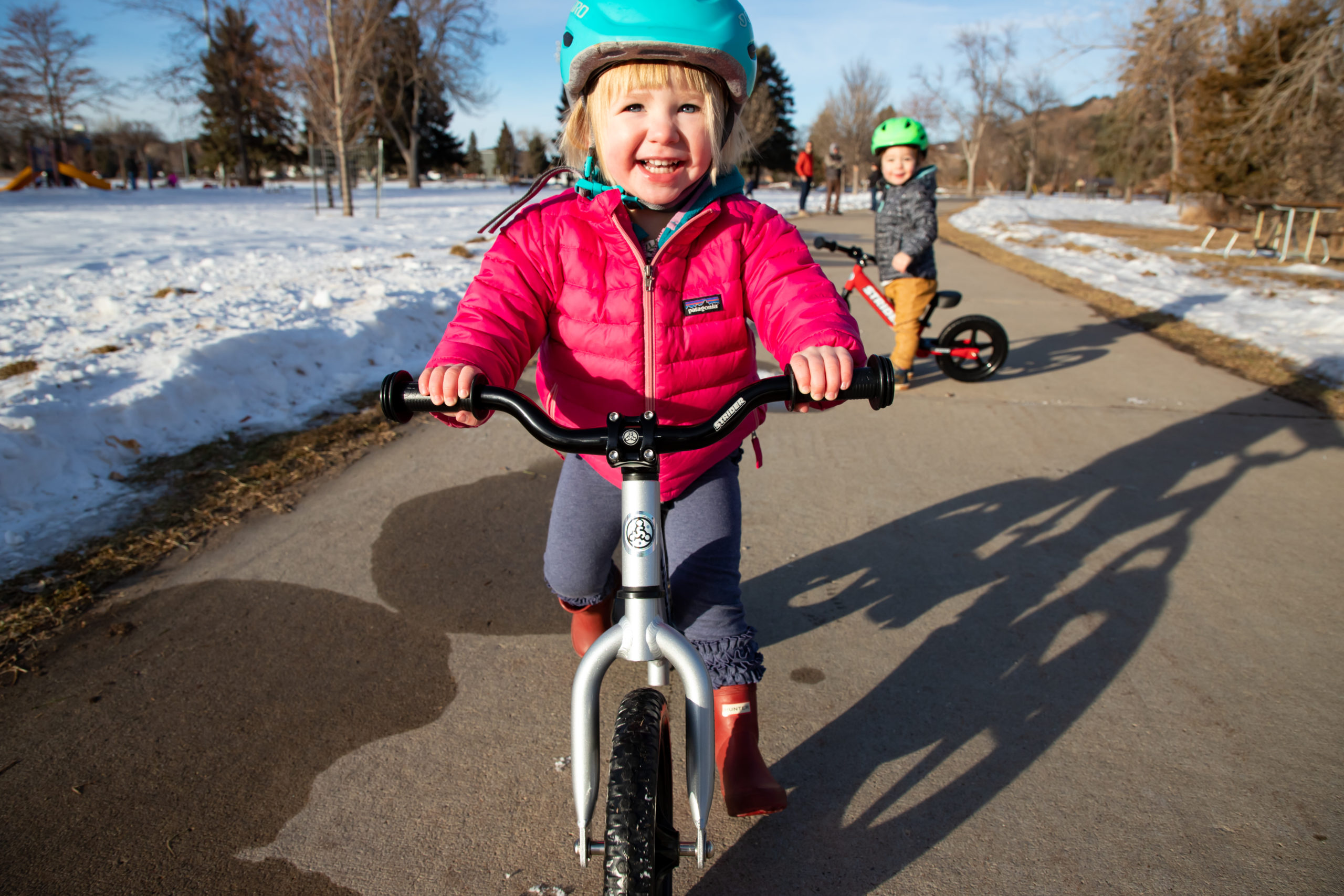 Young toddler girl striding with a smile on silver 12 Pro with Strider Aluminum Riser Bars