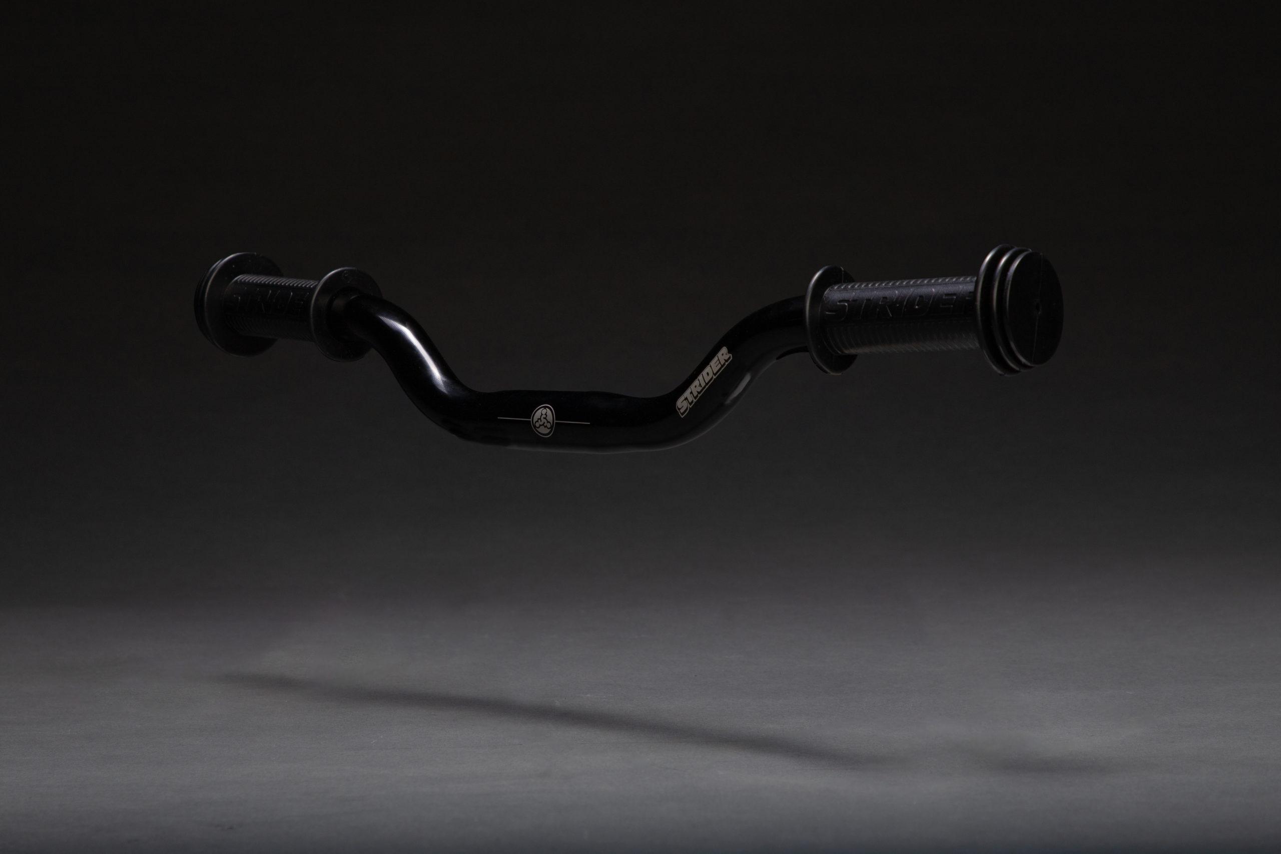 Dark studio image of Strider Aluminum Riser Handlebars with Grips