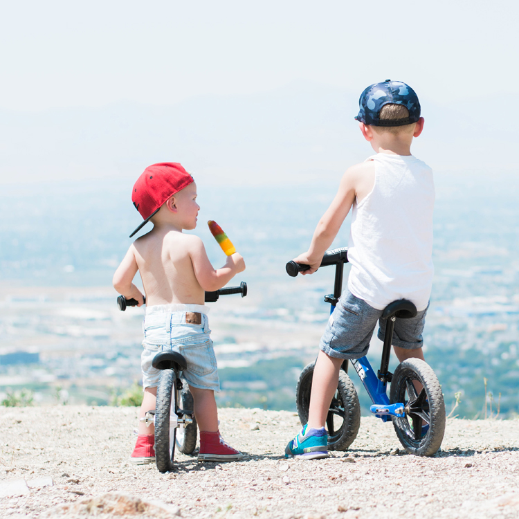 Boys wearing hats, eating popsicles, and looking out at city view on their Strider 12 Sports