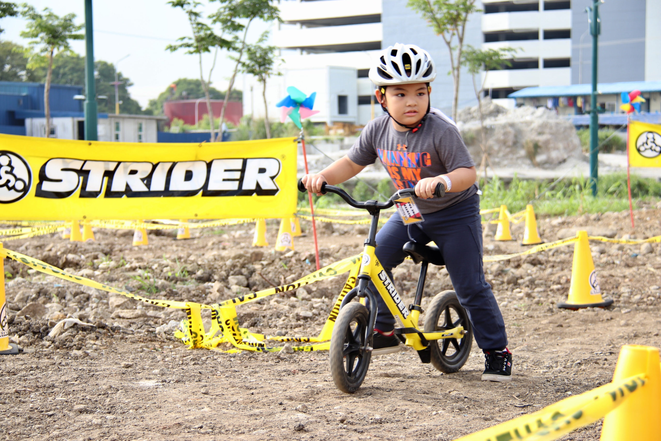 Young boy racing yellow 12 Sport with foot brake attached
