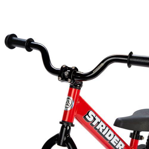 A studio shot of the Strider Aluminum High-Rise Wide handlebar on a red balance bike